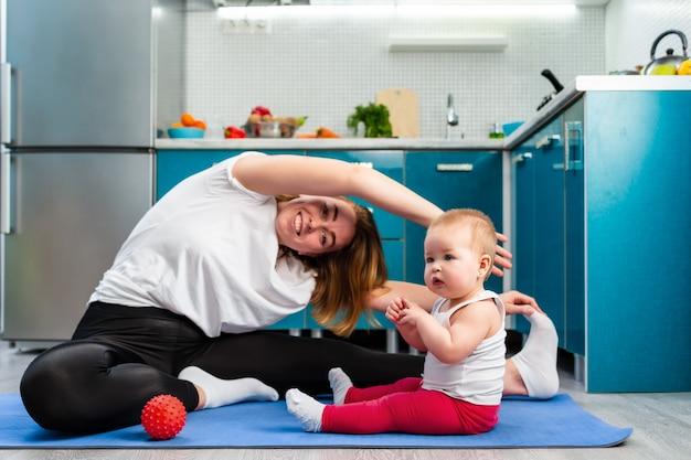 Uma jovem mãe está fazendo ioga em um tapete na cozinha, e seu bebê está sentado ao lado dela
