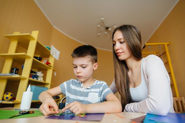 Uma jovem mãe está fazendo lição de casa com o filho em casa. pais e treinamento