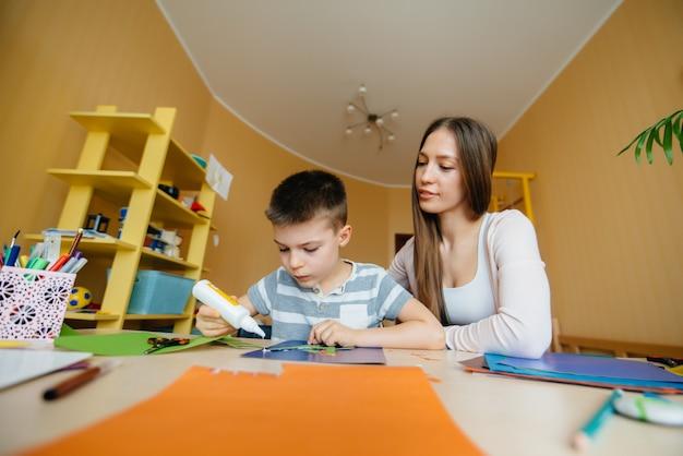 Uma jovem mãe está fazendo lição de casa com o filho em casa. pais e treinamento.