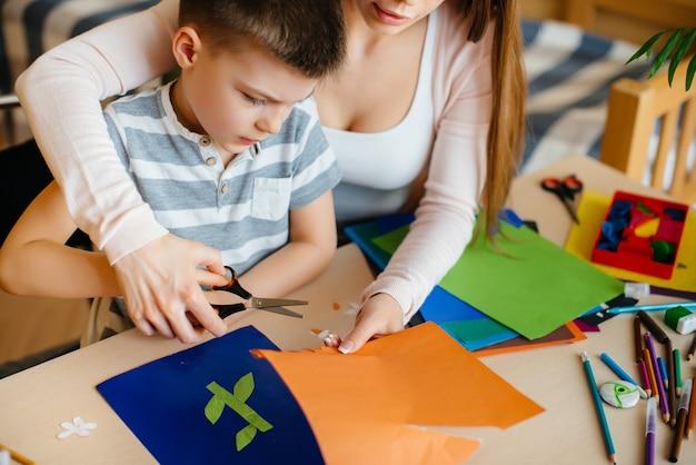 Uma jovem mãe está fazendo lição de casa com o filho em casa.