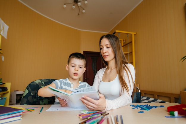 Uma jovem mãe está fazendo lição de casa com seu pai em casa. pais e treinamento.