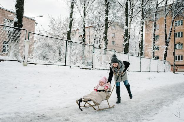 Uma jovem mãe feliz caminha com o bebê e um trenó infantil ao ar livre no inverno.