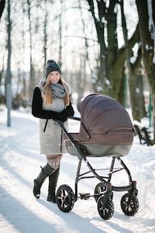 Uma jovem mãe feliz caminha com um carrinho e um bebê em um parque de inverno.