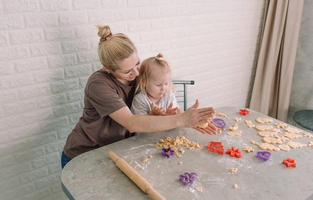 Uma jovem mãe feliz e sua filha juntas preparam deliciosos biscoitos sentados à mesa