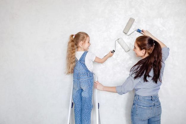 Uma jovem mãe feliz fica ao lado de sua filha e eles seguram rolos nas mãos e fazem reparos em casa.