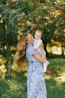 Uma jovem mãe feliz mantém seu filho nos braços contra os ramos de rowan com bagas, eles são alegres. feliz maternidade e infância