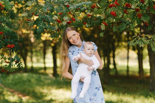 Uma jovem mãe feliz mantém seu filho pequeno nos braços