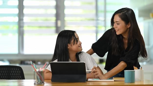 Uma jovem mãe fica e tutoria sua filha na mesa do estudante de madeira por tablet computador.