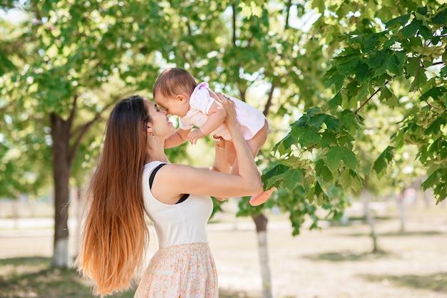 Uma jovem mãe linda com uma filha nas mãos, passear no parque.