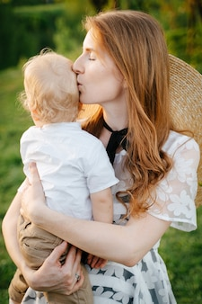 Uma jovem mãe ruiva acalma seu filho bebê segurando-o nos braços e beijando na cabeça contra o pano de fundo do dia das mães verde