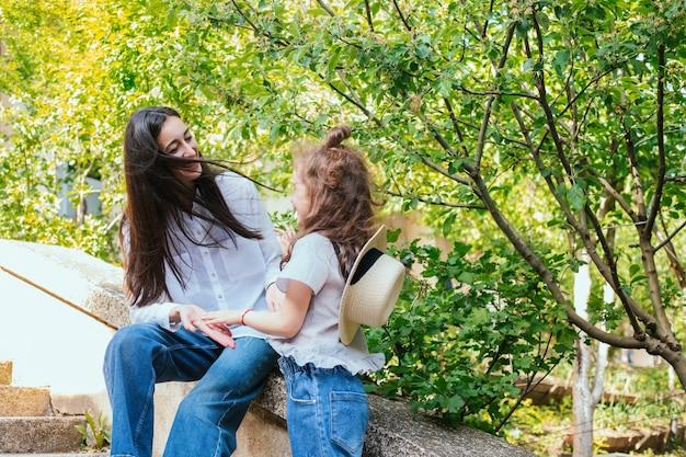 Uma jovem mãe segura a mão da filha e fala. o conceito de família forte, amor materno e ternura.