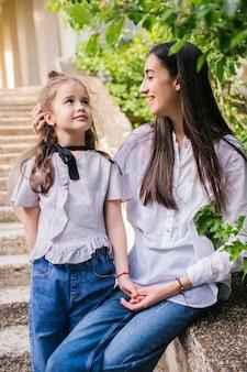 Uma jovem mãe segura a mão da filha e fala. o conceito de uma família forte.
