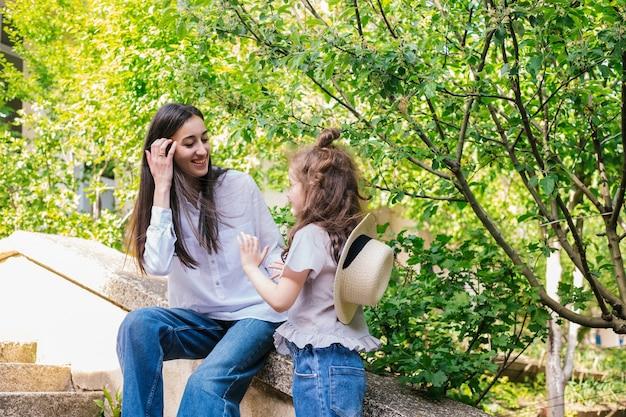 Uma jovem mãe segura a mão da filha e fala.