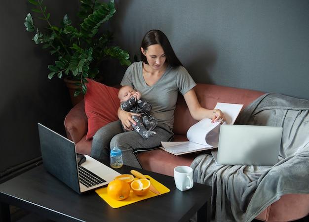 Uma jovem mãe segura um bebê e trabalha em casa com documentos e laptops