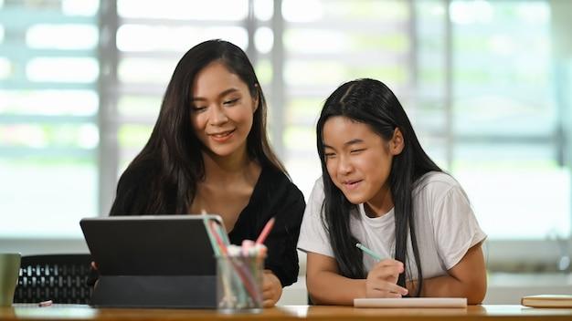 Uma jovem mãe senta-se e fazendo lição de casa junto com a filha na mesa do estudante de madeira.