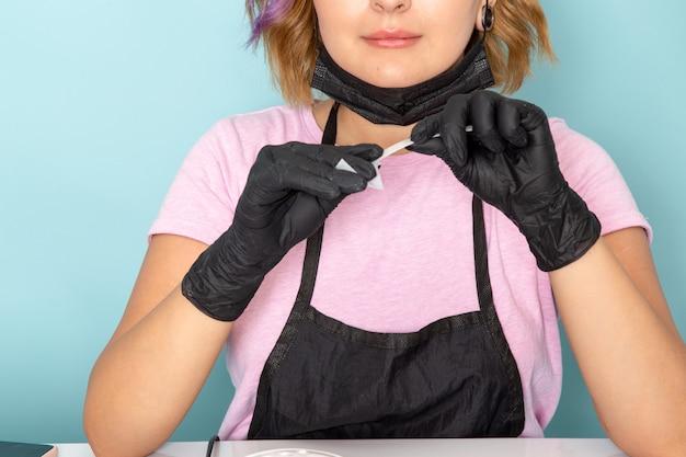 Uma jovem manicure feminina de frente para uma camiseta rosa e capa preta com luvas pretas segurando detalhes de manicure em azul