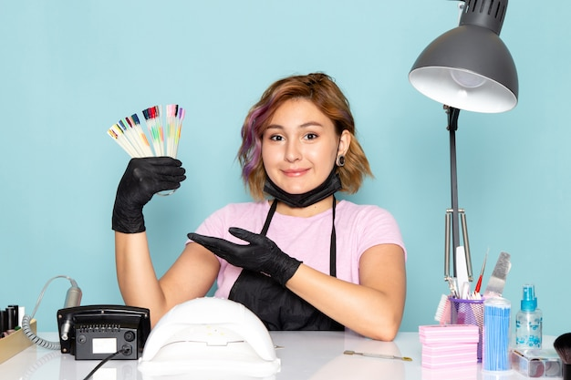 Uma jovem manicure feminina, de vista frontal, com camiseta rosa e capa preta com luvas pretas se preparando para o trabalho em azul