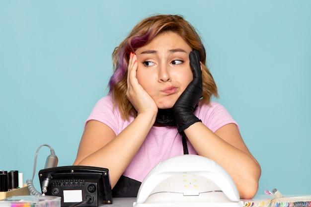 Uma jovem manicure feminina de vista frontal com uma camiseta rosa com luvas pretas e máscara preta ficando entediada com o azul