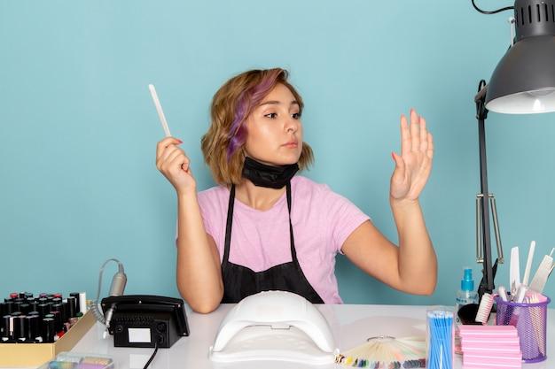 Uma jovem manicure feminina, vista frontal, com uma camiseta rosa com luvas pretas e máscara preta, sentada em frente à mesa, trabalhando com as unhas no azul