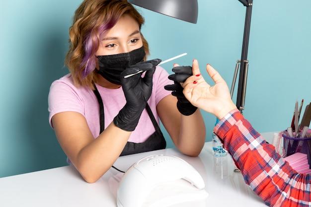 Uma jovem manicure feminina, vista frontal, com uma camiseta rosa com luvas pretas e uma máscara preta fazendo manicure em azul