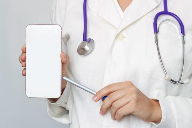 Uma jovem médica apontando para uma tela branca de telefone celular com um espaço vazio para texto ou desenho