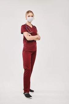 Uma jovem médica com um uniforme médico e uma cobertura protetora para o rosto, isolado no branco