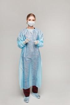 Uma jovem médica em uma cobertura protetora e máscara segurando um tubo endotraqueal no fundo azul, isolado. conceito de saúde e emergência.