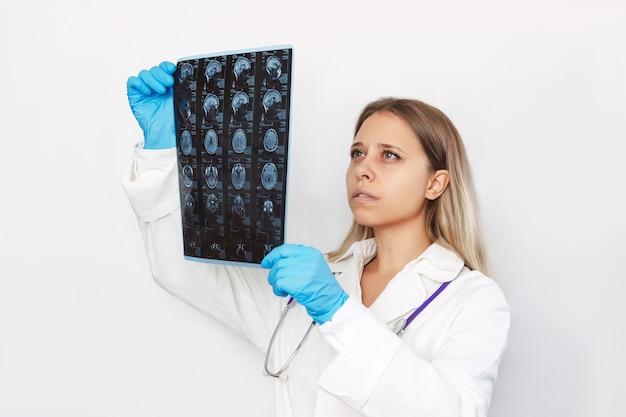 Uma jovem médica loira examinando ressonância magnética da cabeça e do cérebro de um paciente segurando-a