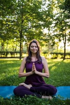 Uma jovem medita sobre um tapete de ioga na natureza