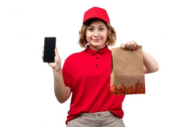 Uma jovem mensageira com boné vermelho de camisa vermelha segurando um pacote de entrega e um smartphone sorrindo