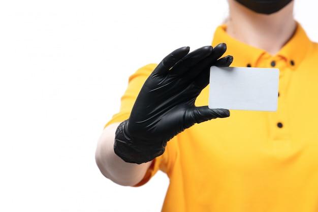 Uma jovem mensageira com uniforme amarelo, luvas pretas e máscara preta segurando um cartão branco