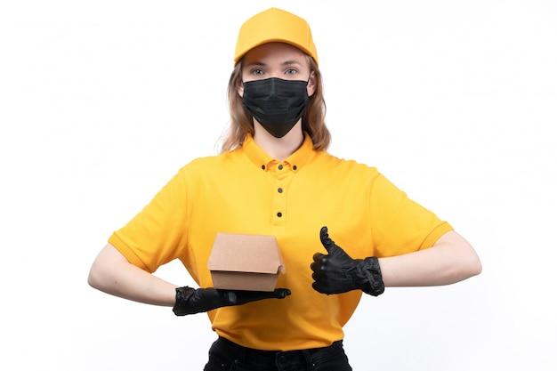 Uma jovem mensageira com uniforme amarelo, luvas pretas e máscara preta segurando um pacote de comida