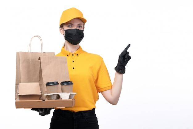 Uma jovem mensageira com uniforme amarelo, luvas pretas e máscara preta, segurando xícaras de café e pacotes