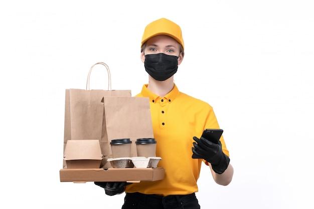 Uma jovem mensageira com uniforme amarelo, luvas pretas e máscara preta, segurando xícaras de café, telefone e pacotes