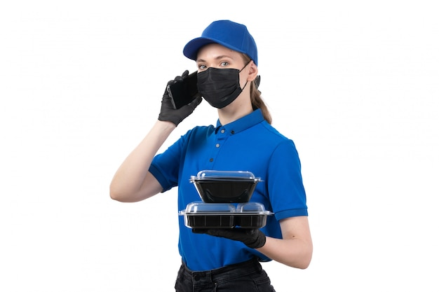 Uma jovem mensageira com uniforme azul, luvas pretas e máscara preta, segurando tigelas de entrega de comida e telefone
