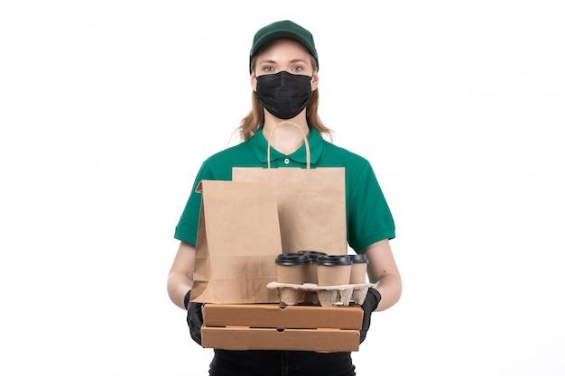 Uma jovem mensageira com uniforme verde, luvas pretas e máscara preta, segurando pacotes de entrega de comida