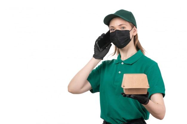 Uma jovem mensageira com uniforme verde, luvas pretas e máscara preta, segurando um pacote de entrega de comida e um telefone