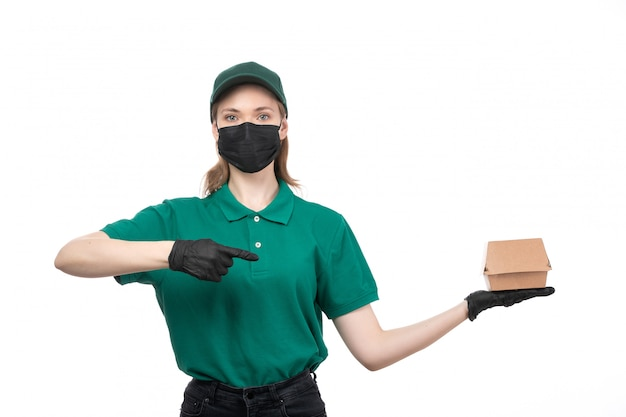 Uma jovem mensageira com uniforme verde, luvas pretas e máscara preta, segurando um pacote de entrega de comida