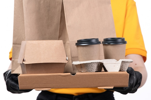 Uma jovem mensageira de frente com luvas pretas de uniforme amarelo e máscara preta segurando caixas de pizza e xícaras de café