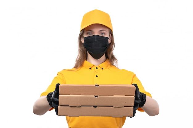 Uma jovem mensageira de frente com luvas pretas de uniforme amarelo e máscara preta segurando caixas de pizza