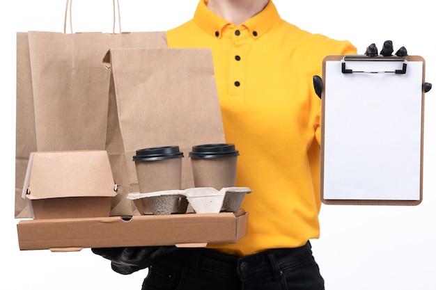 Uma jovem mensageira de frente com luvas pretas de uniforme amarelo e máscara preta segurando pacotes de comida e xícaras de café