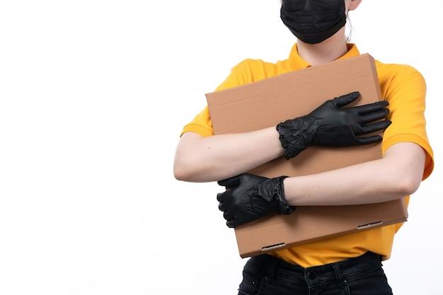 Uma jovem mensageira de frente com luvas pretas de uniforme amarelo e máscara preta segurando um pacote de entrega