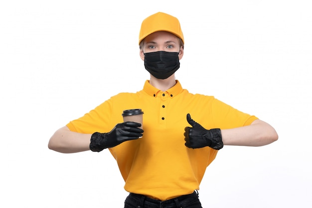 Uma jovem mensageira de frente com luvas pretas de uniforme amarelo e máscara preta segurando uma xícara de café e mostrando um cartaz