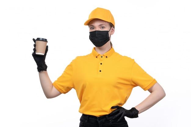 Uma jovem mensageira de frente com luvas pretas de uniforme amarelo e máscara preta segurando uma xícara de café