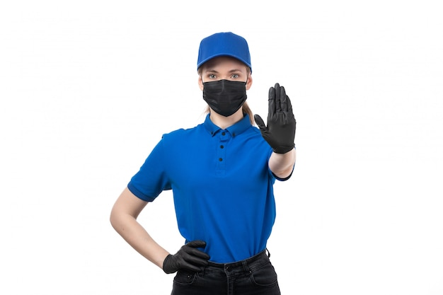 Uma jovem mensageira de frente com luvas pretas de uniforme azul e máscara preta mostrando a placa de pare