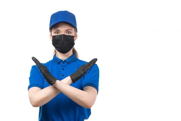 Uma jovem mensageira de frente com luvas pretas de uniforme azul e máscara preta mostrando sinal de proibição