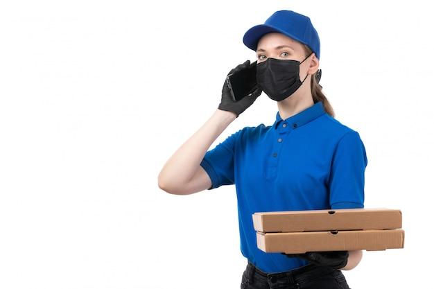 Uma jovem mensageira de frente com luvas pretas de uniforme azul e máscara preta segurando pacotes de entrega de comida e smartphone