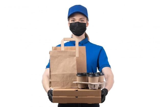 Uma jovem mensageira de frente com luvas pretas de uniforme azul e máscara preta segurando pacotes de entrega de comida