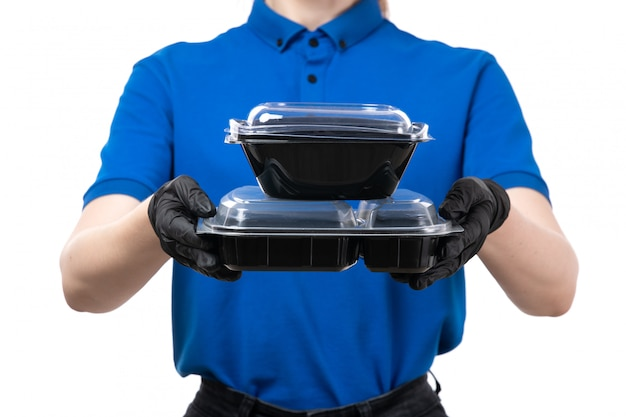 Uma jovem mensageira de frente com luvas pretas de uniforme azul e máscara preta segurando tigelas de entrega de comida