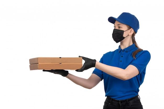 Uma jovem mensageira de frente com uma máscara preta de uniforme azul e luvas segurando pacotes de entrega de comida